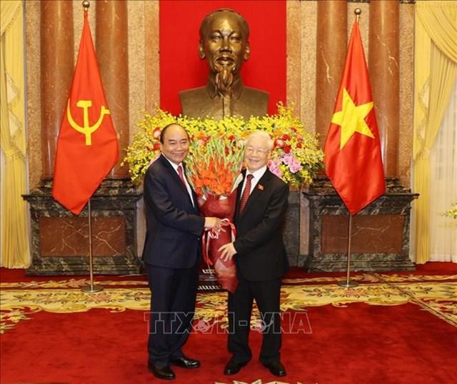 Chủ tịch nước Nguyễn Xuân Phúc tặng hoa Tổng Bí thư Nguyễn Phú Trọng, nguyên Chủ tịch nước. Ảnh: Trí Dũng/TTXVN