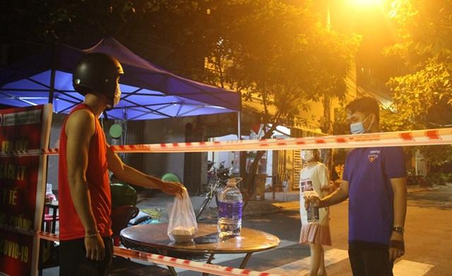 Bạn Mai Đức Minh Tuấn giúp giao nhận đồ cho người dân trong khu cách ly tại chốt đường An Thượng 32, quận Ngũ Hành Sơn.